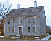 A light blue wooden house with a pointed gray roof, two white chimneys and pale cream-colored window and door trim