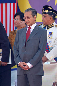 A photo showing former Prime Minister Mahatir bin Mohamad standing with head down and surrounded by government officials at the celebration of the 50th independence day.