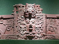 Section of stucco frieze with a prominent human face in the centre, surrounded by elaborate decoration.