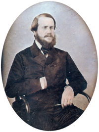 A photograph of a young bearded man seated in an armchair with his right hand tucked into the front of his double-breasted jacket