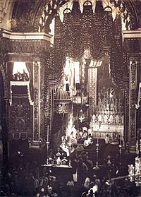 Looking down upon an assembly in a large, vaulted cathedral with a figure sitting on a large, canopied throne to the left of an altar