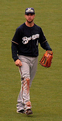 """Portrait of a man in a dark blue baseball jersey with """"BREWERS"""" across the chest, grey pants with dirt on the right knee, a baseball glove on his left hand, and a blue cap with an """"M"""" on it."""