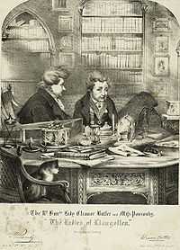 An engraved drawing of two stout Englishwomen sitting in a private library with their hair up in buns and wearing smoking jackets. They are seated at an ornately carved table with various objects on it. A cat sits in the foreground in a chair.