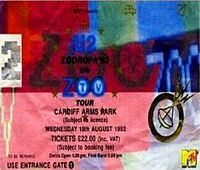 """A multi-coloured rectangular concert ticket, displayed horizontally. Small icons are scattered in the background. It bears the logo of a satellite and features details of the concert, along with the text """"U2 Zooropa '93 Zoo TV Tour""""."""