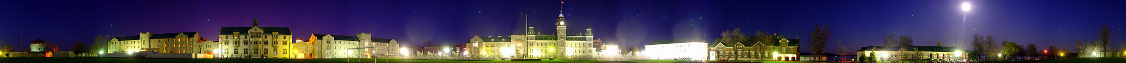 A 260 degree photo of the Royal Military College of Canada in  Kingston, Ontario, on the 4th of May 2007.  Seen is a green landscape during the night, featuring  buildings made of white stone and red brick. The night sky is  dark blue and purple, with the moon shining bright on the right side of the image.  Photo credit: Martin St-Amant (User:S23678)