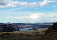 A big river winds through a landscape of sparsely vegetated hills and bluffs. Dark rock faces contrast sharply with a bright blue sky veiled with intermittent white and gray clouds. In the foreground, an open space between bluffs opens on the river.