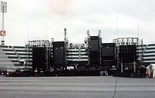 An elaborate concert stage, seen during the day in an empty stadium. The stage comprises several dark, rectangular structures.