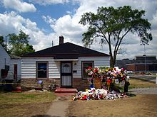 A house surrounded by yellow colored grass, flowers, trees, and a light blue colored sky can be seen. The house has white walls, two windows, a white door with a black door frame, and a black roof. In front of the house there is a walk way, yellow grass and multiple colored flowers and memorabilia. In the background, there are two tall trees and a light blue colored sky that has multiple clouds.