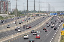 """""""A view of a wide freeway from the side. The freeway is divided into four segments, each of which contains three lanes (up to five in some places). The vehicles within the two sections nearest the camera are travelling away into the distance, whereas the vehicles within two sections further from the camera are approaching. Several signs dot the right side of the freeway, and two overhead gantries (also holding signs) are also visible."""""""