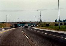 Driving down a six lane highway during the day. In front is a concrete bridge. The highway curves to the right as it passes beneath the bridge.
