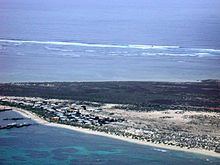 View across a sandy strip of land, with ocean on both sides. The land nearest the observer is mostly sandy, and has many buildings on it, and some jetties. The land furthest from the observer is thickly vegetated. The ocean in the foreground is blue-green, with dark patches indicating areas of coral reef. The ocean in the background is light blue. There is a line of breakers in the distance.