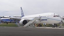 Front/side view of white 787 on static display. Stairway is positioned ahead of the right engine for access into cabin.