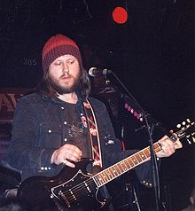 A man playing a guitar and singing on stage. He is wearing a denim jacket and woolen cap