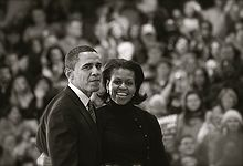 Barack and Michelle Obama, wearing dark outdoor clothes, in front of a crowd. His expression is muted; she has a wide smile.