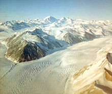 Aerial view: mountain ranges at top and bottom right of picture are separated by a broad ice river.