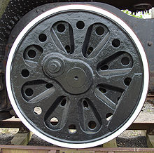 An almost solid disc (not spoked) locomotive wheel with a series of cast-in radial indentations and prominent round holes intended to reduce its weight.
