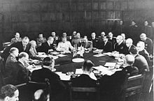 A few dozen men sitting around a circular table with many documents on it