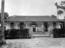 Two men stand on the porch of a single story building behind an open gate lined with bushes
