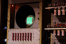 A smalll cathode ray tube in a rusty yellow/brown metal frame showing a green rectangular display of dots and dashes. Below it is a series of 40 red switches arranged in 8 columns of 5.