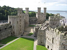 In a picture taken from a high vantage point is seen the courtyard of a castle, surrounded by walls and towers. In the background are seen wooded hills to the left, and ocean and shoreline to the right.