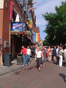 Canal Street during Europride 2003: several rainbow flags adorn the exterior of bars along the road.