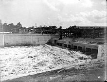 A black and white photograph of a canal lock built in the Everglades, directing millions of gallons of water toward the Atlantic Ocean