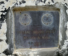 A grey plaque on a white surface with evidence of chipped paint and general decay
