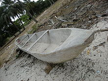 An angled view of a wooden boat lying on the sand with some trees in the background