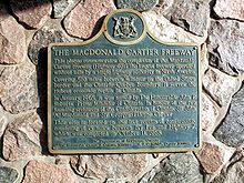 A blue plaque on a stone wall. The plaque has a yellow border, and is mostly rectangular in shape, with the long end oriented horizontally. However, the top side has a camel hump in the centre, with a circle centred at the top of the hump. Inside the circle is an Ontario coat-of-arms. The plaque reads: THE MACDONALD CARTIER FREEWAY This plaque commemorates the completion of the Macdonald-Cartier Freeway (Highway 401), the longest freeway operated without tolls by a single highway authority in North America. Covering 510 miles between Windsor on the United States border and the Ontario-Quebec boundary, it serves the richest economic region in Canada. In January, 1965, it was named by The Honourable John P. Robarts, Prime Minister of Ontario, in honour of the two founding architects of the Confederation of Canada, Sir John A. Macdonald and Sir Georges Etienne Cartier. This site is located on the last section of construction, consisting of 15 miles between Ivy Lea and Highway 2, which was completed on October 11, 1968.