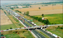 """""""A highway viewed from high above travels into the distance from the bottom-right to the top-left. An overpass allows a road to cross the highway near the bottom of the image. The surroundings are entirely agricultural. On the highway, several dozen vehicles are piled into each other. The middle of the large pileup is smoking."""""""