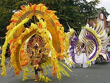 Part of a West Indian carnival procession passes along a public road in front of trees (to the left) and red-brick houses (to the right). In front is a participant wearing a gold helmet and vestigial armour. Above and around her is an enormous shield-shaped yellow, gold and red contraption supported by spokes and with many large feathers. Behind her is another participant in a white dress with a similar-shaped feathered shield contraption in yellow, brown and purple worn the other way up.