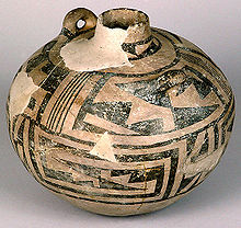 A nearly spherical ceramic vessel, painted with a network of black triangles and lines over a tan surface; many chips and cracks reveal a beige substratum. The top tapers to a short and narrow cylindrical neck. A toroidal carrying handle protrudes outward near it.