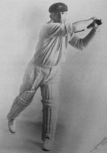 Studio portrait against a white background of a stocky cricketer in white shirt and trousers with rolled up sleeves, cricket pads, baggy green cap with Australia coat of arms, wearing gloves and holding a bat and swinging it horizontally to his left. He is a right-hander and his leading left leg is straight but his right leg is bent with only the toes on the ground.