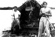 black and white photograph of two men on a raft, fitted with a large hut. The far bank of the river is visible in the far distance