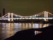 Night view of a lit suspension bridge over a wide river, which reflects the light from the bridge.
