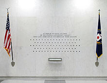 A white wall featuring an inscription, several dozen stars placed in five rows, a book, framed by the U.S. flag on the left and a flag bearing the CIA's seal on the right.