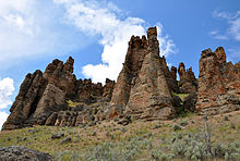 A row of rock spires connected at the base rises toward a partly cloudy blue sky.