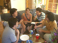 Five people sitting on a couch and a chair in a semicircle around a small table.