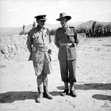 Two officers in tropical military uniforms standing on sandy ground, a larger body of troops is visible in the right background in front of stunted trees and more distant hills