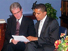 A man with glasses and Obama sit and hold a sheet of paper. Obama points at the paper and talks. Both men wear dark suits and ties.