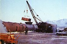 A crane shown loading contamined ice into a large steel tank.