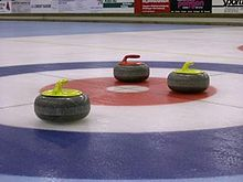 two yellow and one red curling stones on red, white and blue ice