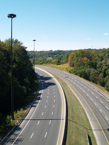 An empty six lane highway in a forested valley