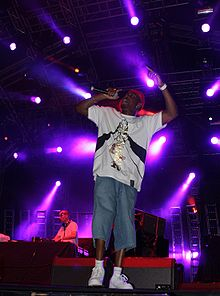 A man rapping on stage, with purple spotlights behind him