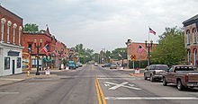 A wide street with a double yellow line and buildings on either side, more on the left than the right. American flags are on the lampposts, and signs both on the road and next to it indicate the railroad crossing in the distance.