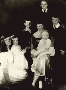 A mother surrounded by her six children of varying ages (two teenagers, two children, one toddler, one baby).