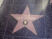 """A five-point star engraved on a tile. In the center of the star are the words """"EARVIN MAGIC JOHNSON"""". An image of a movie camera is etched directly below these words, though still in the star."""