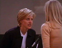 Still shot of a television show from 1997 showing, Ellen DeGeneres leaning forward to speak to a woman with long blond hair seen from behind. In between them is a microphone