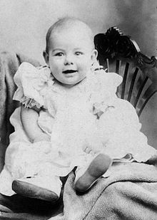 an infant dressed in light colored clothing propped on a chair faces the camera