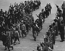 Several lines of school children march diagonally from top right to bottom left. Each carries a bag or bundle and each raises their right arm in the air in a salute. Adults stand in a line across the bottom right hand corner making the same gesture.
